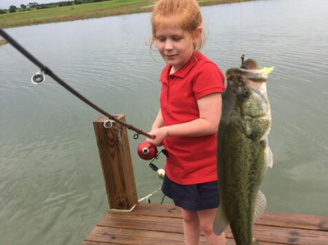 girl in red blouse holding bass on fishing rod