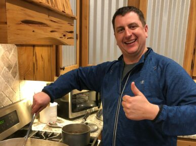 man holding thumbs up while stirring gumbo