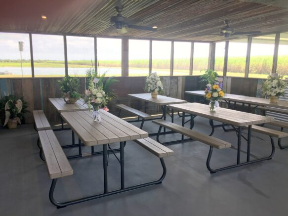 picnic tables with flowers under pavilion
